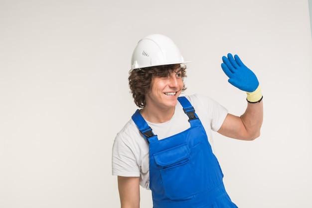 白いヘルメットと青い全体的に彼の手を振って、コピースペースのある白い壁で笑っているハンサムなビルダーの肖像画