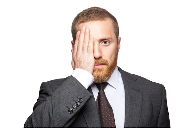 彼がカメラを直接見ているときに彼の手で片目を覆っているハンサムなビジネスマンの肖像画。白い背景で隔離。