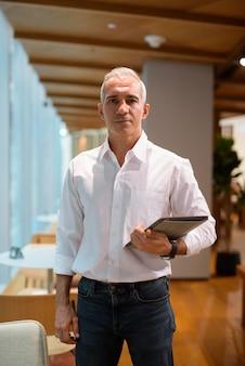 커피숍 세로 샷에서 디지털 태블릿을 들고 있는 잘생긴 사업가의 초상화
