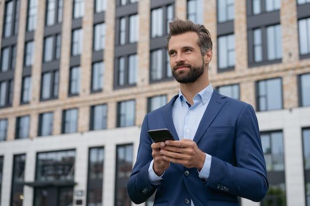 Портрет красивого бизнесмена, держащего мобильную телефонную связь онлайн успешный бизнес