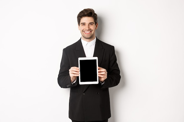 흰색 배경에 서서 디지털 태블릿 화면을 보여주고 웃고 있는 세련된 정장을 입은 잘생긴 사업가의 초상화