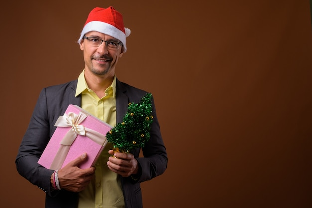 Портрет красивого бизнесмена, готового к рождеству на коричневом