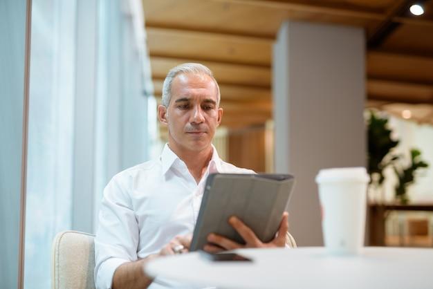 커피숍에 앉아 디지털 태블릿을 사용하는 잘생긴 사업가의 초상화