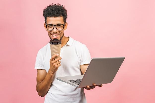 Портрет красивого случайного афро-американского молодого человека, пьющего кофе, держа ноутбук