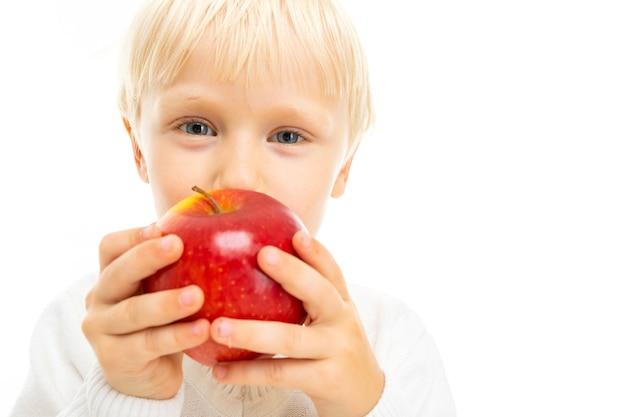 Портрет красивого кавказского мальчика со светлыми волосами и белой кожей в белой блузке и синих шортах ест красное яблоко