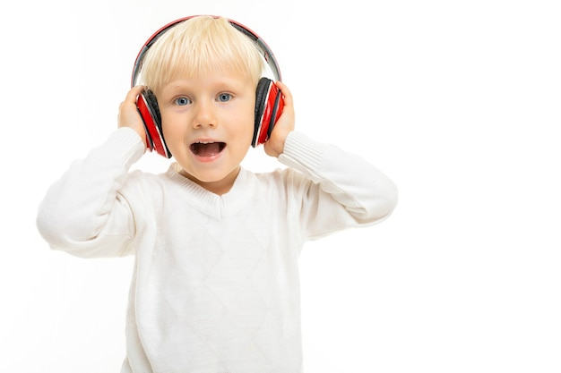 Портрет красивого кавказского мальчика со светлыми волосами и белой кожей в белой блузке и синих шортах слушает музыку