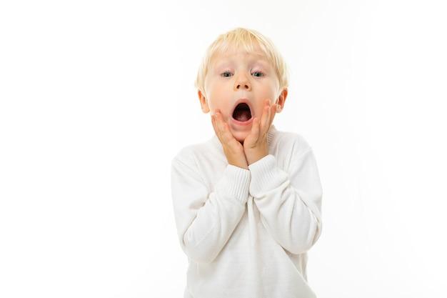 Портрет красивого кавказского мальчика со светлыми волосами и белой кожей в белой блузке и синих шортах кричит