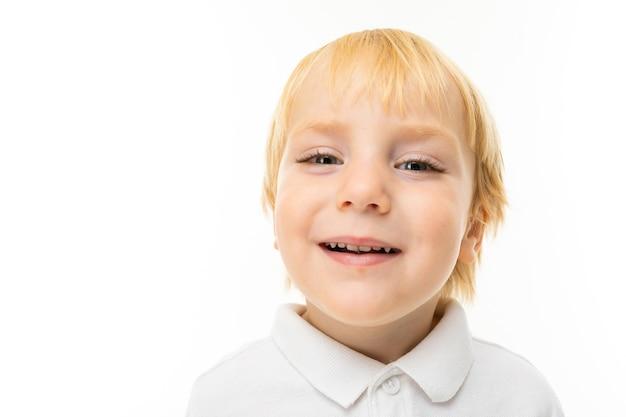 Портрет красивого кавказского мальчика со светлыми волосами и белой кожей в белой блузке и синих шортах улыбается