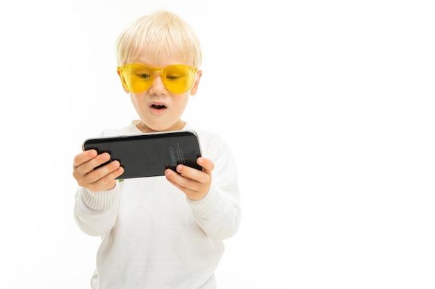 Портрет красивого кавказского мальчика со светлыми волосами и белой кожей в белой блузке и синих шортах с желтыми очками серфинга в интернете