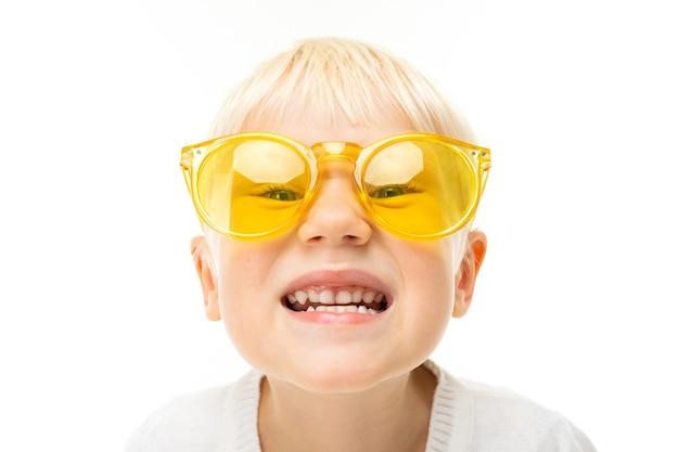 Портрет красивого кавказского мальчика со светлыми волосами и белой кожей в белой блузке и синих шортах с улыбками в желтых очках