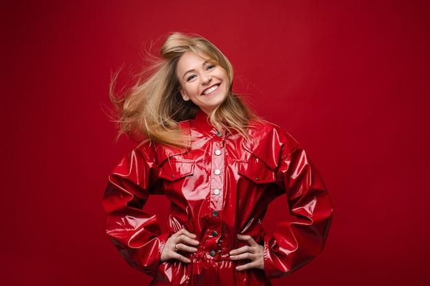 Портрет красивой кавказской девушки с длинными светлыми волосами в красном кожаном костюме наслаждается своей жизнью