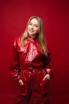 Портрет красивой кавказской девушки с длинными светлыми волосами в красном кожаном костюме держит руки в карманах