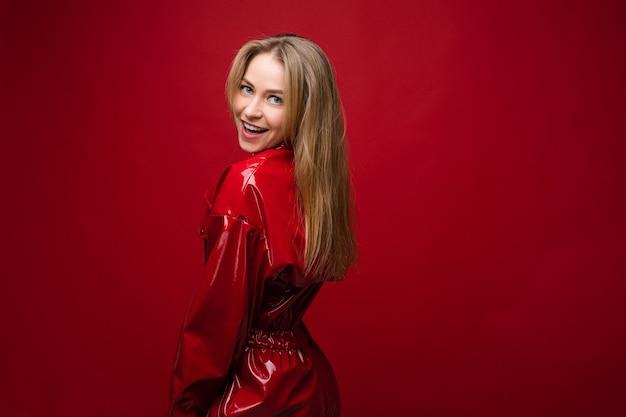 Портрет красивой кавказской девушки с длинными светлыми волосами в красном кожаном костюме улыбается
