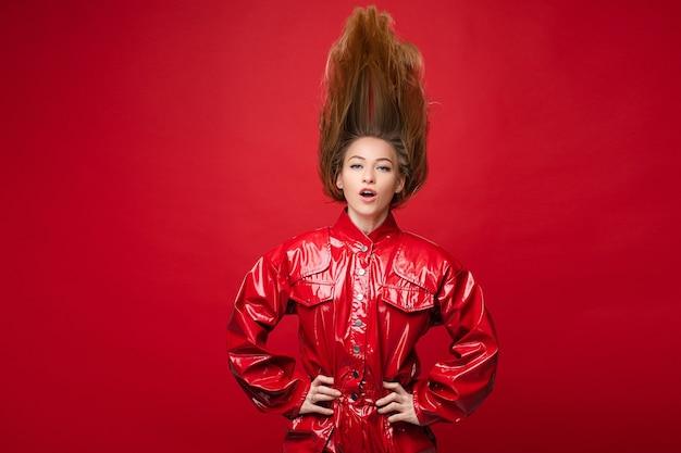 Портрет красивой кавказской женщины с длинными светлыми волосами сверху в красном кожаном костюме висит