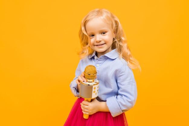 長い金髪、きれいな顔のドレスを着たハンサムな白人の女の子の肖像画は喜んでマイクで遊ぶ
