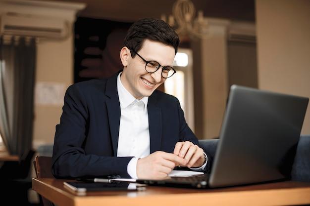 眼鏡のドレッシングスーツを着て彼のラップトップを見ながら笑っている彼の机に座っているハンサムな白人マネージャーの肖像画。