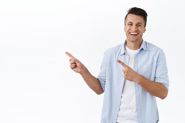 ハンサムな陽気な男の肖像画、製品を広く笑って、指を左に向けて笑って、店を訪問することをお勧めします、リンクをクリックして、宣伝してください、白い壁