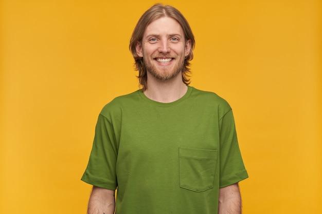금발 헤어 스타일과 수염을 가진 잘 생기고 쾌활한 남자의 초상화. 녹색 티셔츠를 입고. 넓게 웃고있다. 사람과 감정 개념. 노란색 벽 위에 절연