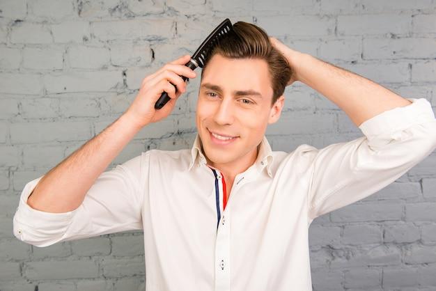 彼の髪をとかすハンサムな陽気な若い男の肖像画