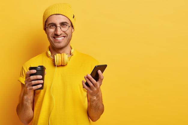 喜んでいる表情でハンサムな陽気な若い男の肖像画、携帯電話を保持し、友人にテキストメッセージを送信し、持ち帰り用のコーヒーを飲み、眼鏡をかけ、ヘッドフォンで黄色の服を着る