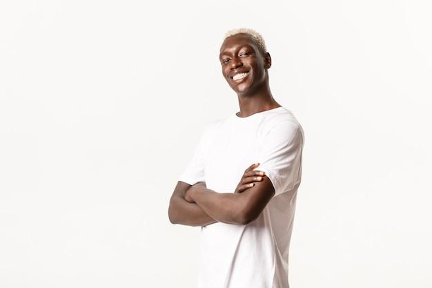 Портрет красивого уверенного афро-американского блондина, скрещенного на груди и улыбающегося нахального и напористого