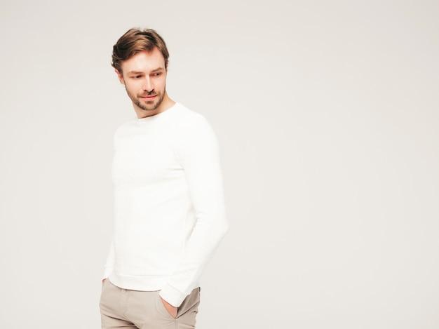 カジュアルな白いセーターとズボンを身に着けているハンサムな自信を持って流行に敏感な腰痛のビジネスマンモデルの肖像画