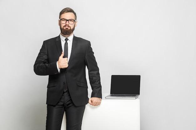 インテリジェンス黒のスーツを着たハンサムな自信を持って成功したひげを生やした青年実業家の肖像画は、彼の職場の近くに立って、親指を立てています。孤立した、スタジオショット、屋内、灰色の背景