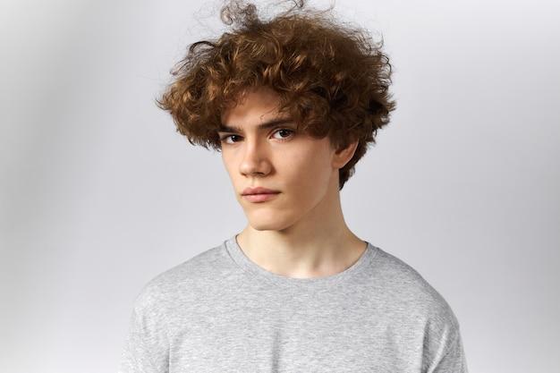 방대한 머리카락, 갈색 눈 및 부드러운 얼굴을 가진 잘 생긴 멋진 십대 소년의 초상화는 심각한 자신감 표정으로 카메라를 응시하는 캐주얼 회색 티셔츠를 입고 있습니다. 피부 관리 및 청소년 개념