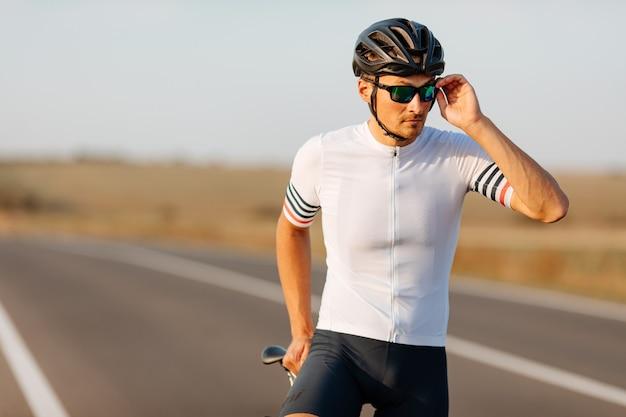 검은 헬멧, 미러 안경 및 야외에서 포즈를 취하는 스포츠 의류에 잘 생긴 사이클의 초상화