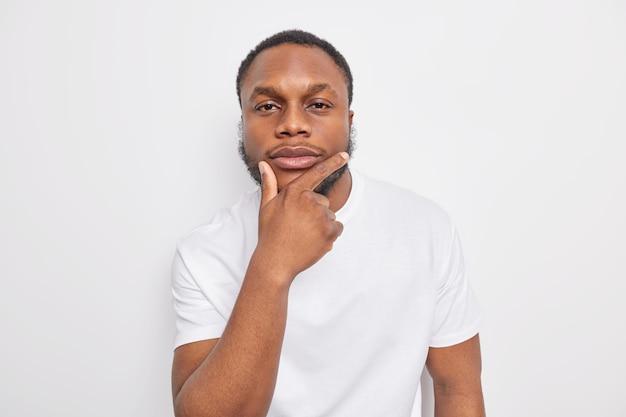 Портрет красивого темнокожего мужчины, держащего подбородок, смотрит прямо в камеру Бесплатные Фотографии