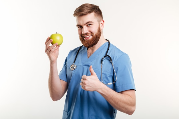 Портрет красивого доктора в голубом пальто смотря камеру