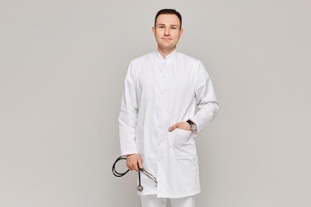 회색 배경에 청진 기 의료 유니폼 포즈 잘 생긴 의사의 초상화.