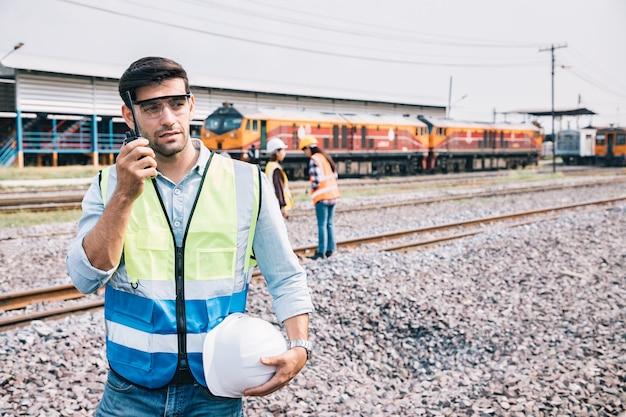 鉄道の制御にトランシーバーを使用するハンサムなエンジニアのポートレート