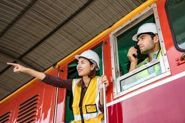 Портрет красивого инженера и помощника, использующего рацию для управления работой в поезде