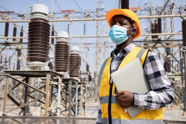 ラップトップを保持し、高出力発電所の前でヘルメットを着用してハンサムなエンジニアリングの男の肖像画。近代的な建物の背景に請負業者の背面図。