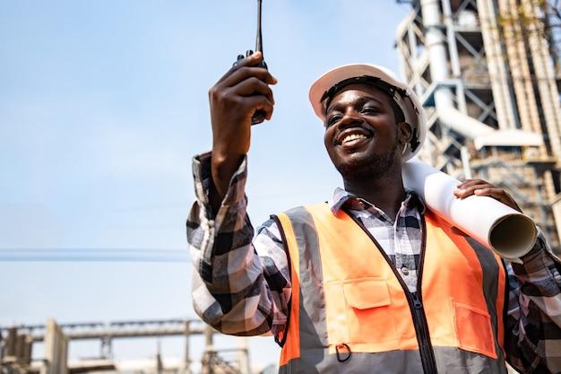 トランシーバーを使用し、石油産業工場の前でヘルメットを着用して書類を保持しているハンサムなエンジニアリングの男の肖像画。近代的な建物の背景に請負業者の背面図。