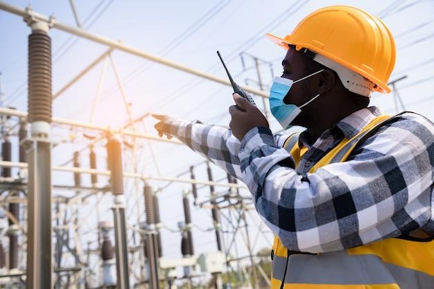 トランシーバーを使用し、高出力発電所の前でヘルメットを着用してハンサムなエンジニアリングの男の肖像画。近代的な建物の背景に請負業者の背面図。