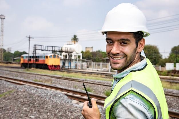 Портрет красивого инженера, использующего рацию с изношенной каской перед гаражом