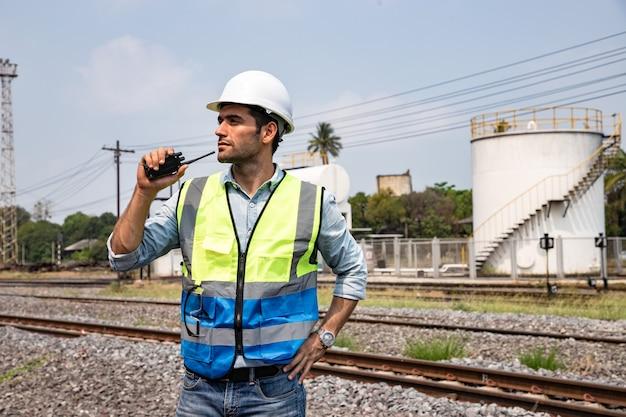 電車のガレージの前でハードハットを着用したトランシーバーを使用したハンサムなエンジニアリングのポートレート