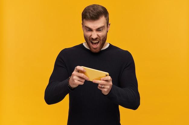ブルネットの髪とひげを持つハンサムで興奮する男性の肖像画。ピアスあり。黒のセーターを着ています。彼のスマートフォンでビデオゲームをプレイしています。黄色い壁の上に隔離されたスタンド