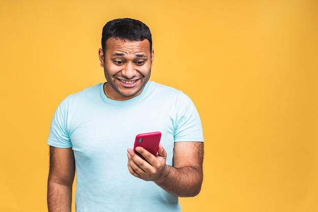 노란색 배경에 격리된 연인에게 캐주얼한 옷을 입고 메시지를 주고받는 흥겹고 즐거운 인도 흑인 남성의 초상화. 전화 사용.