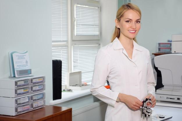 Портрет красивого глазного врача, стоящего с офтальмологическим устройством в кабинете, копией пространства