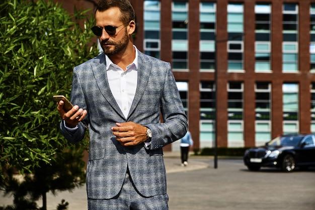 通りでポーズをとってエレガントな市松模様のスーツに身を包んだハンサムなファッション実業家モデルの肖像