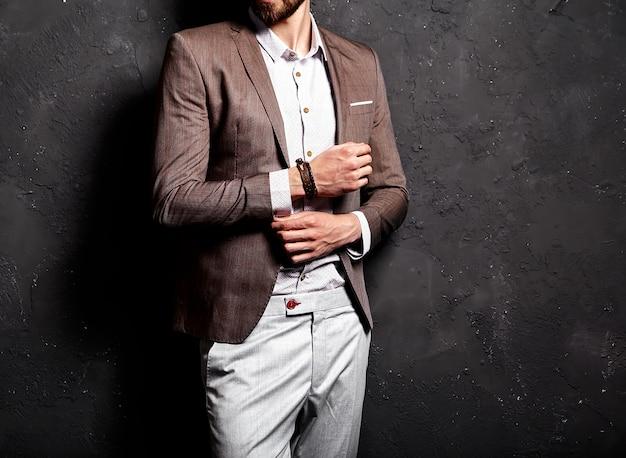 暗い壁の近くのエレガントな茶色のスーツに身を包んだハンサムなファッションスタイリッシュな流行に敏感なビジネスマンモデルの肖像画