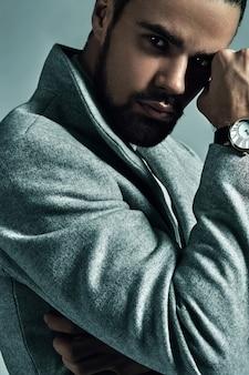 スタジオでポーズをとって暖かいオーバーコートに身を包んだハンサムなファッションスタイリッシュなヒップスターモデルの肖像画。