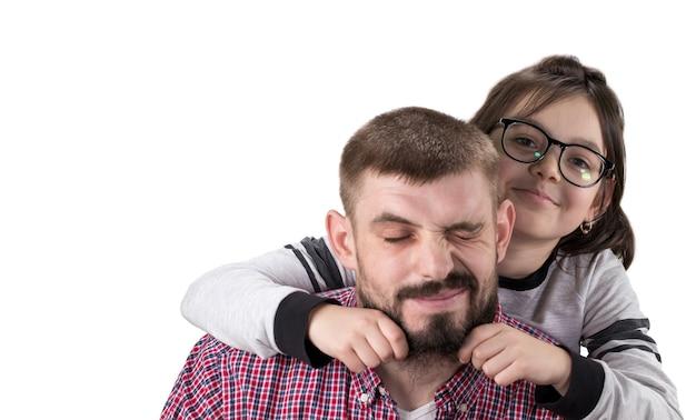 Портрет красивого отца и его милая дочь, обнимая, глядя в камеру и улыбаясь.