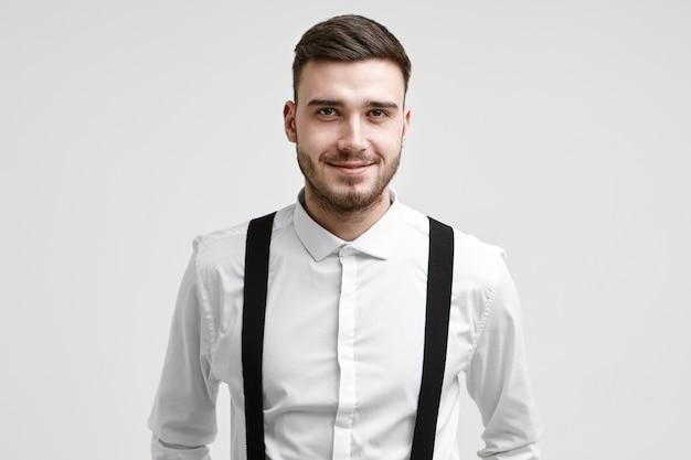 スタイリッシュなヘアカットと髭を持ったハンサムでフレンドリーな若い企業労働者の肖像画は、彼が昇進した後、良い気分で、幸せな自信を持って笑顔でカメラを見ています。仕事と雇用