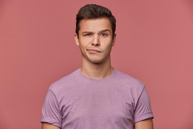 ハンサムな眉をひそめている若い男の肖像画は、空白のtシャツを着て、笑顔と疑いでカメラを見て、ピンクの背景の上に立っています。