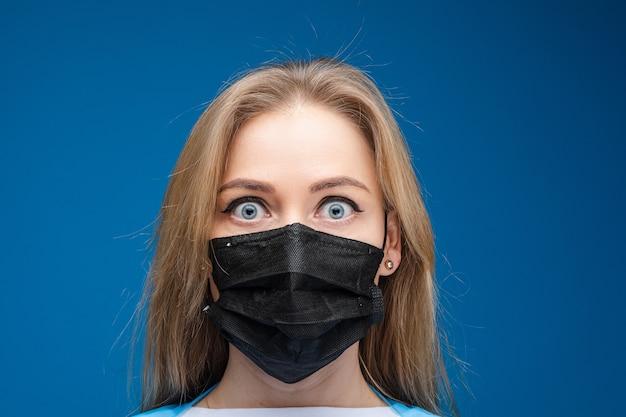 그녀의 얼굴에 의료 마스크와 긴 공정한 머리를 가진 잘 생긴 여자의 초상화