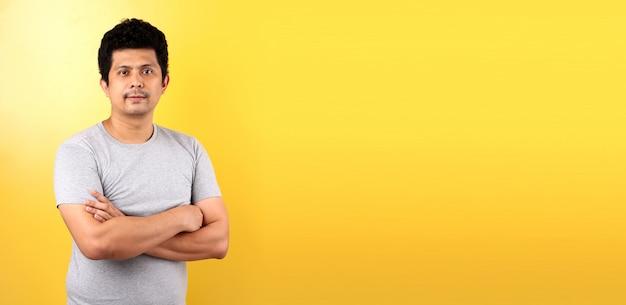 Портрет красивого хорошего смотря азиатского человека изолированного на желтой стене.